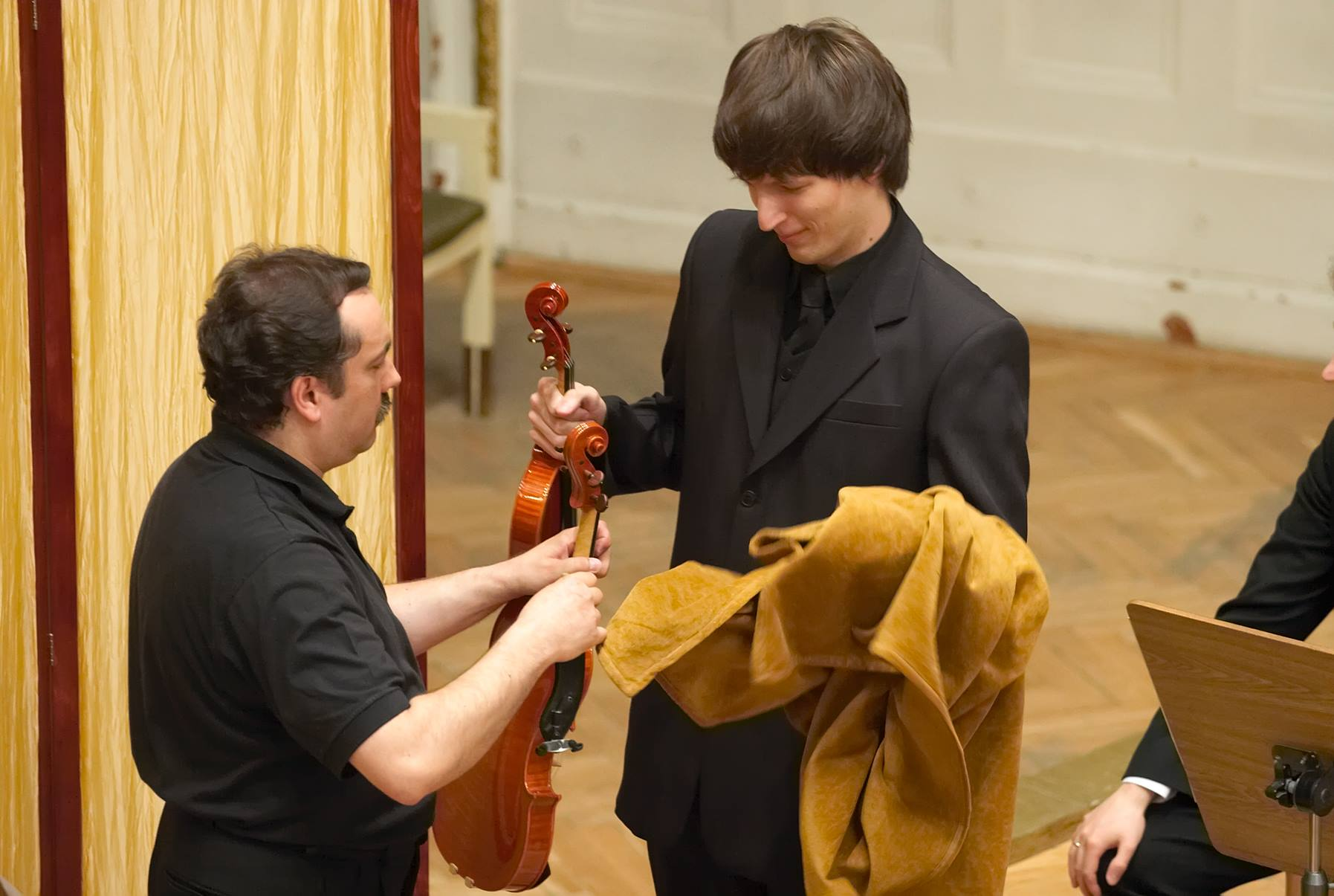 Bartosz Bryła receiving another violin to test at the final stage of the competition.